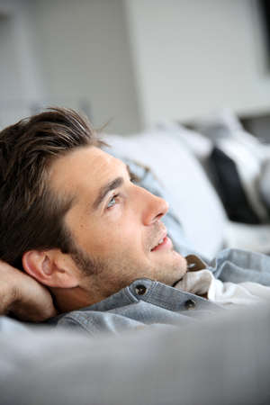man behind: Man relaxing in sofa with arms behind head Stock Photo
