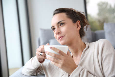 relaxed woman: Peaceful woman relaxing at home with cup of tea