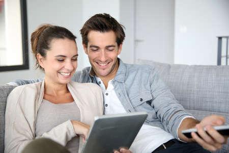 femmes souriantes: Couple � la recherche de programmes de t�l�vision sur internet Banque d'images