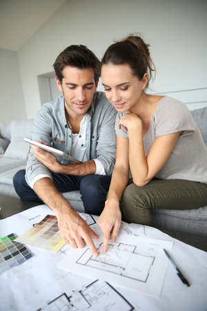 adult couple: Couple searching ideas to decorate new home