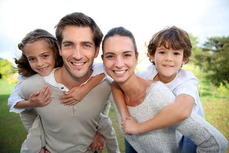 Ouders die op de rug rit naar kinderen