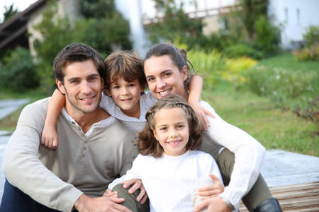 Parents with kids relaxing in front of home photo