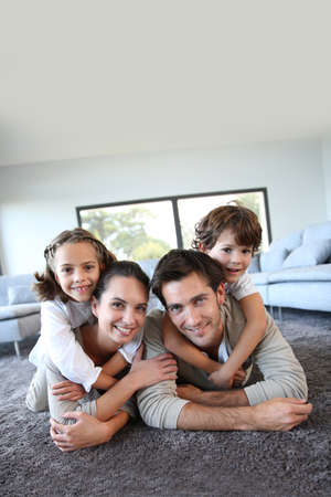 child portrait: Family at home relaxing on carpet Stock Photo