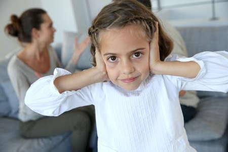pareja discutiendo: Niña tapándose los oídos para no oír los padres argumentando