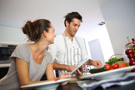 copule: Copule en la cocina de su casa mirando la receta en la web