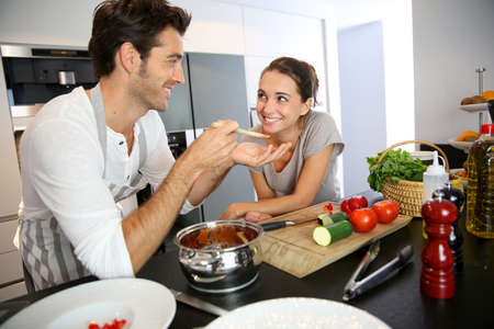 사람은 자신의 아내 맛 파스타 요리를 갖는 스톡 콘텐츠
