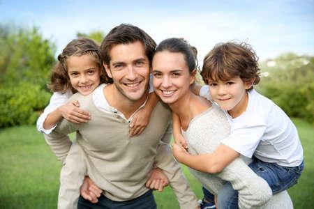 parejas felices: Los padres que dan a cuestas paseo a los niños
