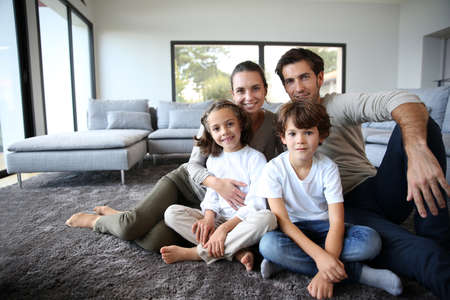 home sweet home: Happy family portrait at home sitting on carpet