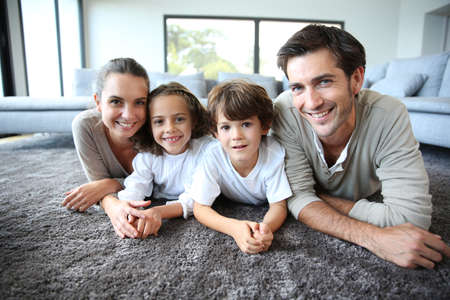 family house: Family at home relaxing on carpet Stock Photo