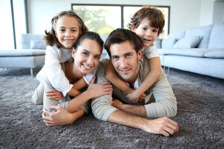 at resting: Family at home relaxing on carpet Stock Photo
