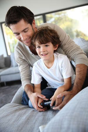 Daddy with kid playing video game photo