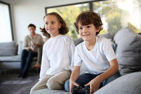 niños jugando videojuegos: Niños en casa jugando videojuegos Foto de archivo