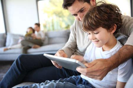 ni�os jugando videojuegos: Padre e hijo que juegan con la tablilla digital