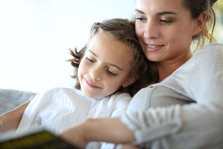 mom and kids: Mom with little girl reading book in sofa