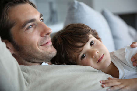 single parent: Boy with daddy relaxing on his chest Stock Photo