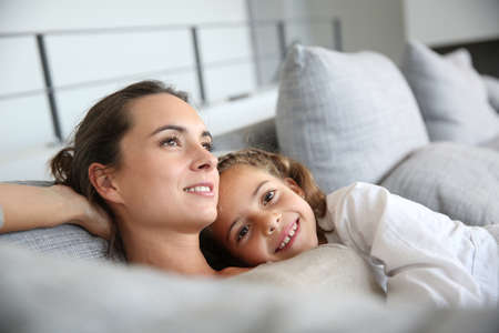 single moms: Mom and little girl relaxing in sofa Stock Photo