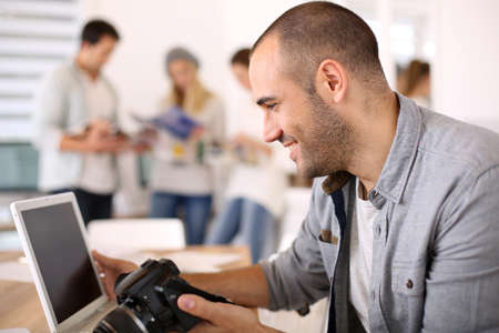 journalists: Cheerful reporter working in office on laptop