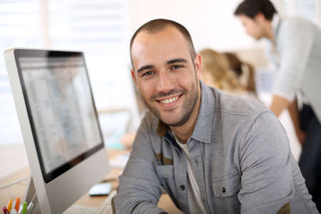 old man: Cheerful guy sitting in front of desktop computer