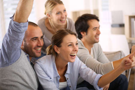 Cheerful group of friends watching football game on tv photo