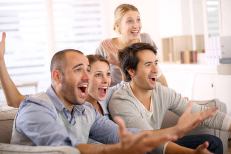 personas mirando: Grupo alegre de amigos viendo el partido de fútbol en la televisión Foto de archivo