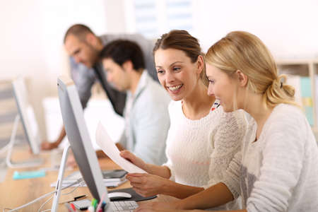 computer training: College girls working in front of desktop