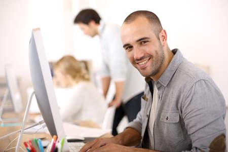 ordinateur de bureau: Joyeux gars assis devant l'ordinateur de bureau Banque d'images