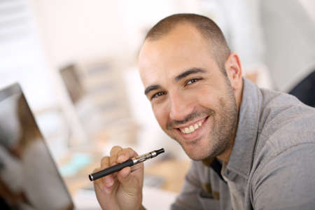 Portrait of cheerful guy smoking with e-cigarette photo
