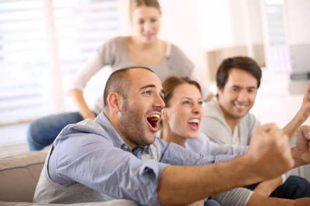 man shouting: Cheerful group of friends watching football game on tv