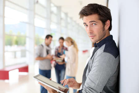 young man: Young man in college campus connected on tablet Stock Photo