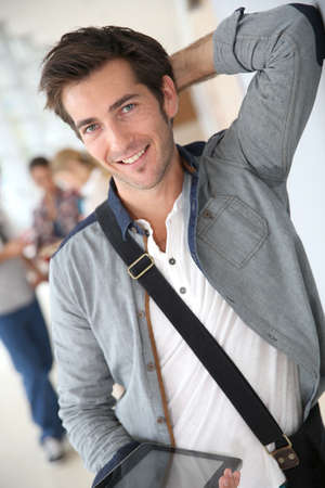 Handsome relaxed young man in school hallway photo