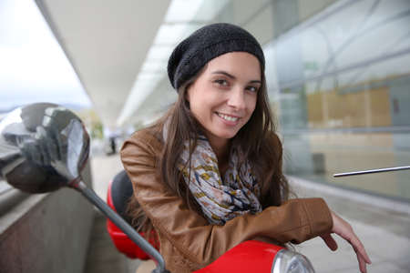attractive young woman: Attractive young woman sitting on red scooter