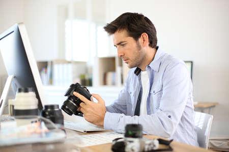 デスクトップ コンピューターで作業してオフィスでカメラマン