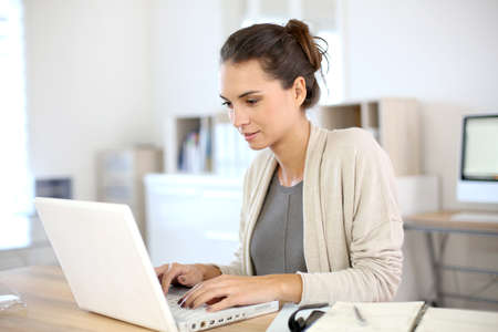 Attractive woman working in office on laptop Stock Photo