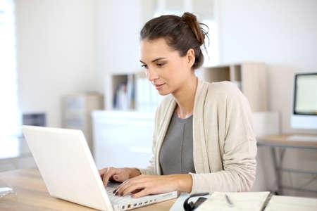 trabajando: Mujer atractiva que trabaja en la oficina en la computadora portátil Foto de archivo