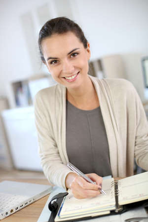 office notes: Businesswoman writing on agenda in office