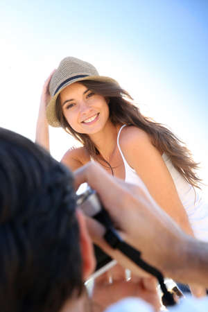 Man taking picture of beautiful woman at the beach photo