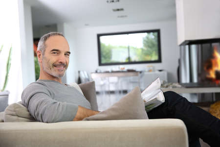 Senior man reading newspaper by fireplace