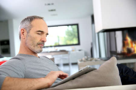 50 years old man: Mature man at home websurfing on internet