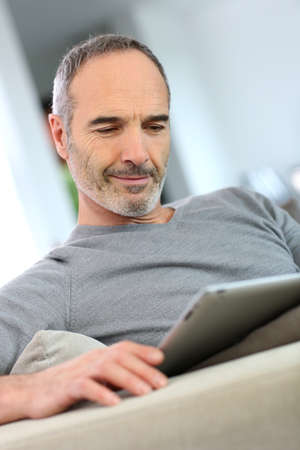 Mature man at home websurfing on internet  photo