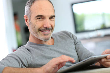 guy person: Mature man at home websurfing on internet