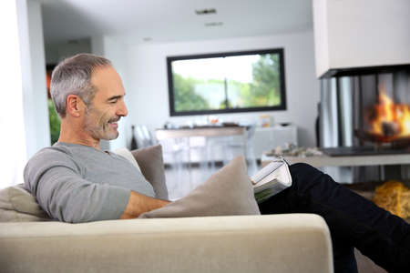 Senior man reading newspaper by fireplace photo