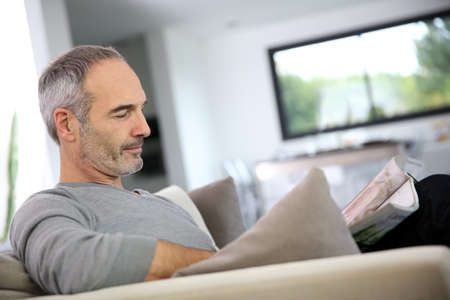 Senior man reading newspaper sit in couch photo
