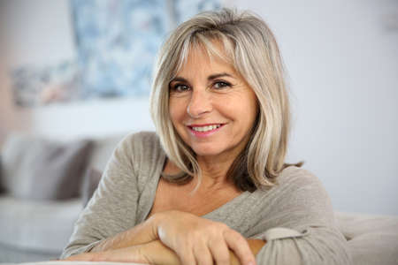 Smiling senior woman sitting in couch at home photo