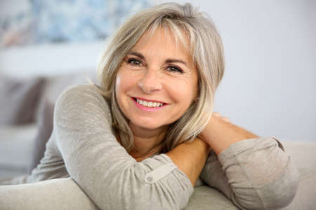 old woman: Smiling senior woman sitting in couch at home