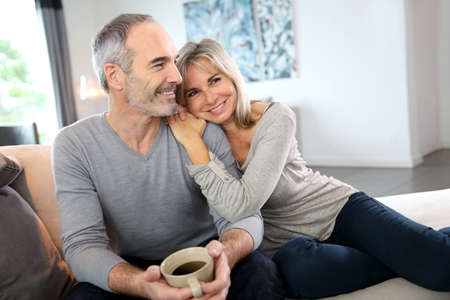 modern love: Romantic senior couple relaxing in couch  Stock Photo