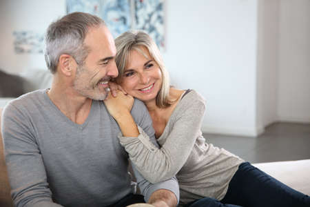pareja abrazada: Rom�ntica pareja senior se relaja en el sof� Foto de archivo