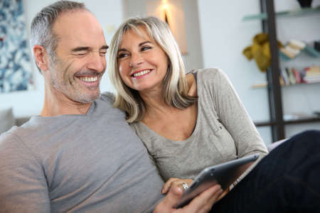 Mature couple at home websurfing with tablet photo