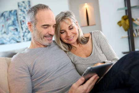 happy retirement: Mature couple at home websurfing with tablet