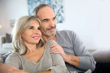 Senior couple sitting in couch and watching tv photo