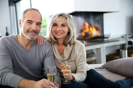 Happy senior couple enjoying glass of champagne photo